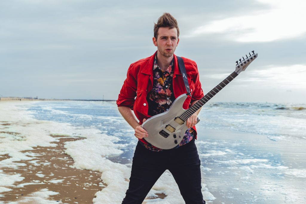 Paul Ozz with a beautiful metal Aristides guitar, standing on a windy beach